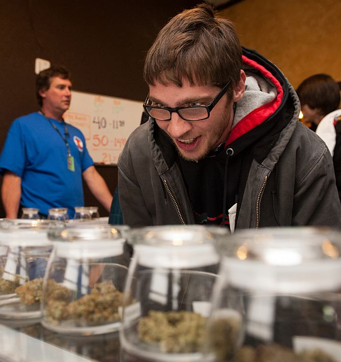 Tyler Williams of Blanchester, Ohio selects marijuana strains to purchase at the 3-D Denver Discrete Dispensary on January 1, 2014 in Denver, Colorado