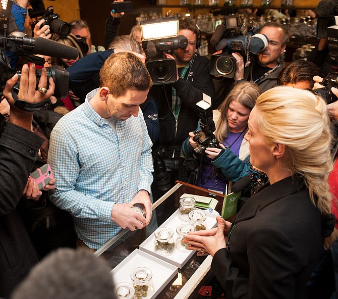 Sean Azzariti, a veteran of the Iraq war, prepares to make the first legal recreational marijuana purchase in Colorado from advocate Betty Aldworth at the 3-D Denver Discrete Dispensary