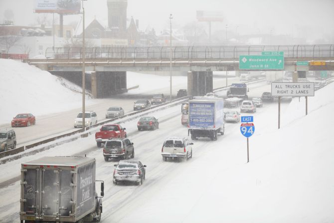 Motorists drive along a snow covered Interstate-94 in Detroit, Michigan on Friday