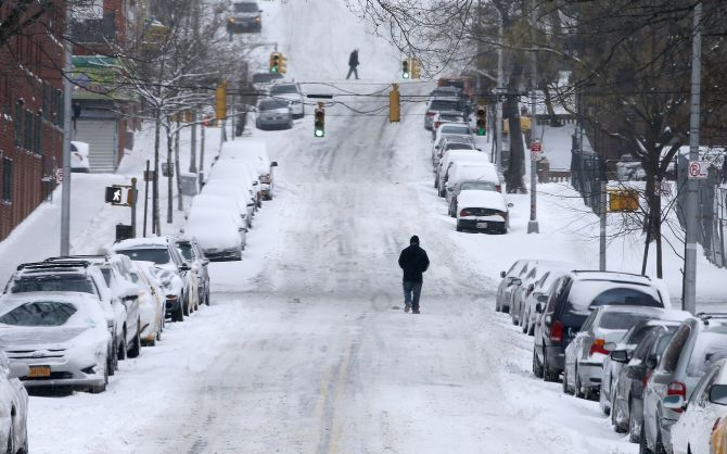 A man walks through snow covered streets in the South Bronx section of New York City, on Friday