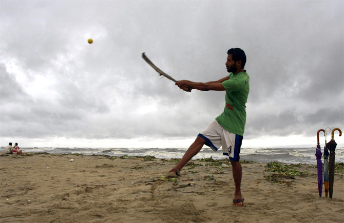 A man plays cricket on a beach in Kerala