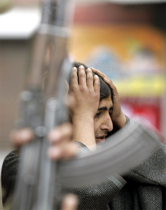 A Kashmiri boy holds his head after he was beaten by policemen during a protest against the arrest of a youth after a gun-battle between security forces and Hizbul Mujahideen militants