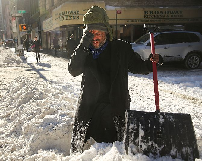 Diego Ramos, who is homeless and lives under nearby building scaffolding, pauses as he clears a sidewalk of snow in lower Manhattan following a snow storm that left up to eight inches of snow
