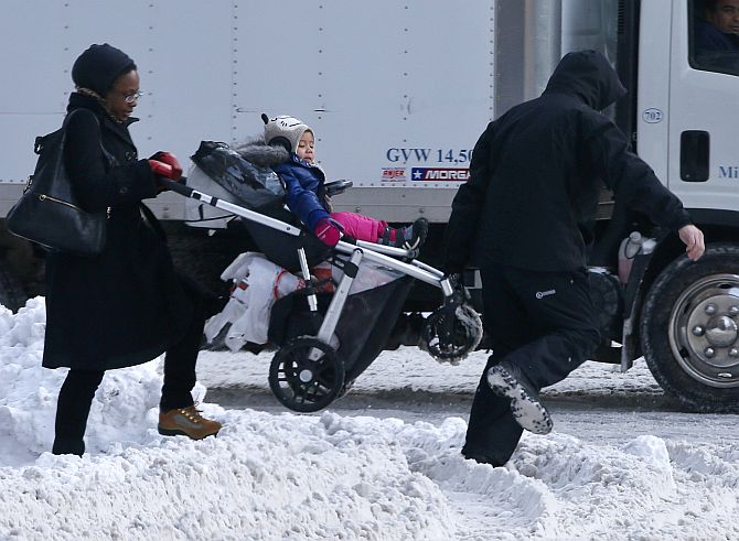A man helps a woman carry a child in a stroller through a snow covered crosswalk in midtown Manhattan in New York City