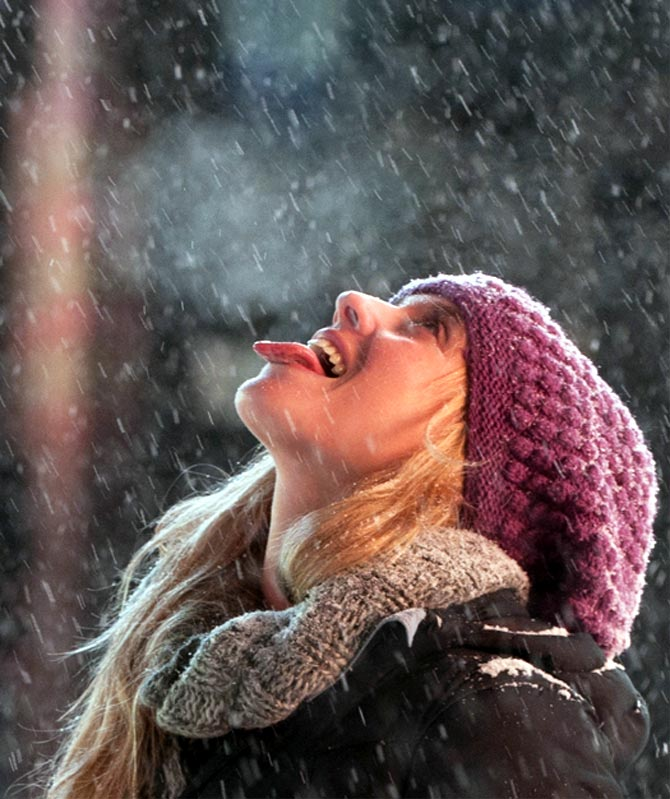A tourist catches snowflakes on her tongue
