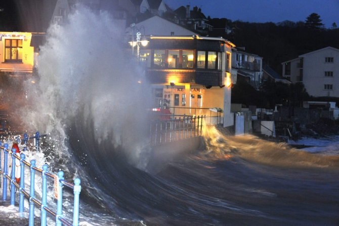 Waves crash over the promenade at hightide in Saundersfoot, in west Wales