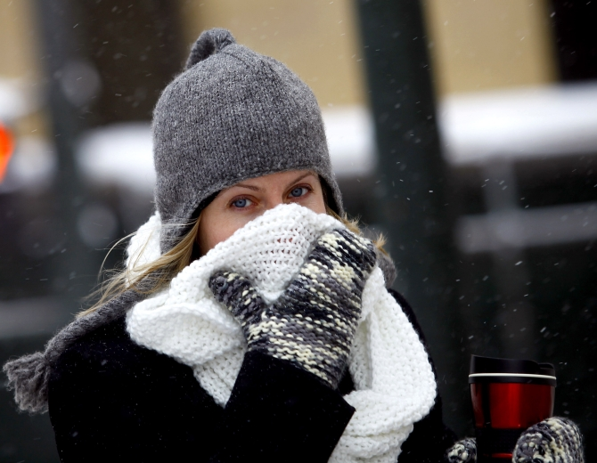A woman covers her face from the cold as the area deals with record breaking freezing weather