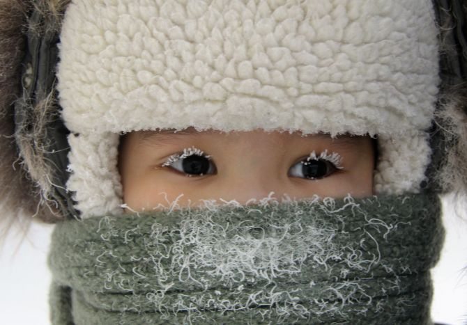 A child, with eyelashes covered with hoarfrost, is seen along a street in the eastern Siberian city of Yakutsk in Sakha (Yakutia) Republic