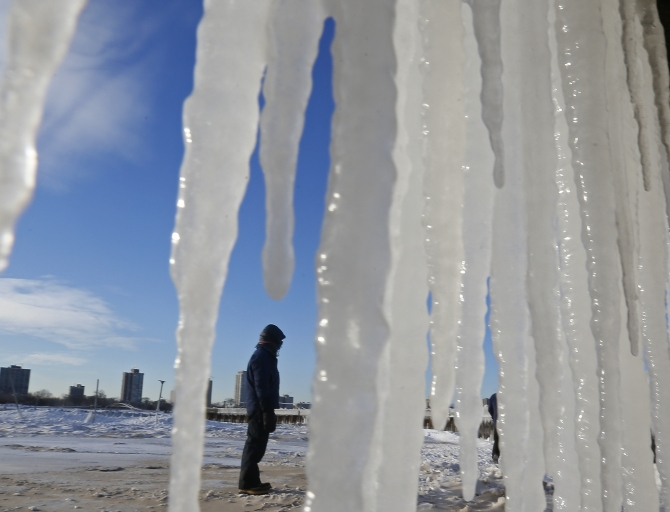 A man is framed by icicles along a beach