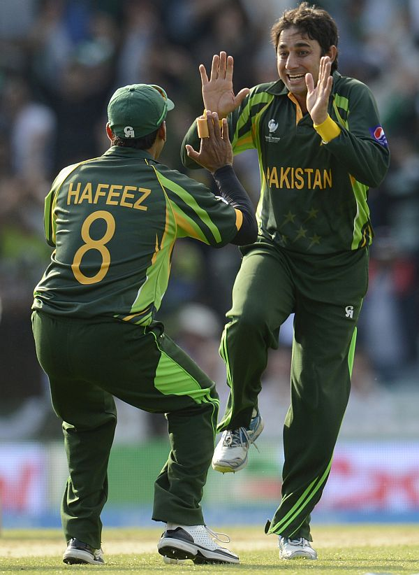 Pakistan's Saeed Ajmal and Mohammad Hafeez celebrate the fall of a wicket during a match against India