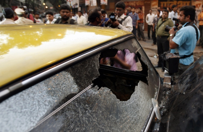 Onlookers and photographers gather near a taxi, ransacked and damaged by the followers of Maharashtra Navnirman Sena, in Mumbai.