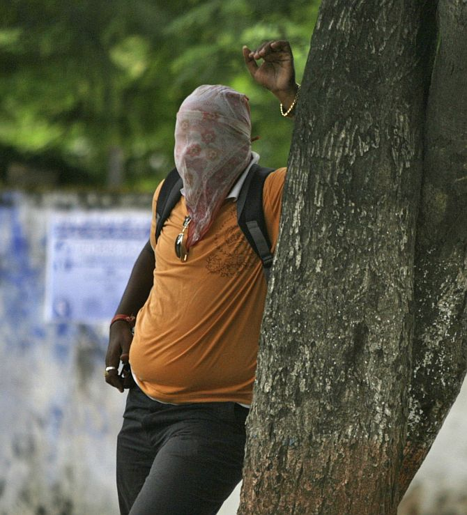 An arsonist hides behind the tree to to avoid tear gas smoke thrown by the riot police.