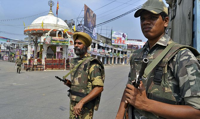 Soldiers stand guard on a deserted street during a curfew in Muzaffarnagar.