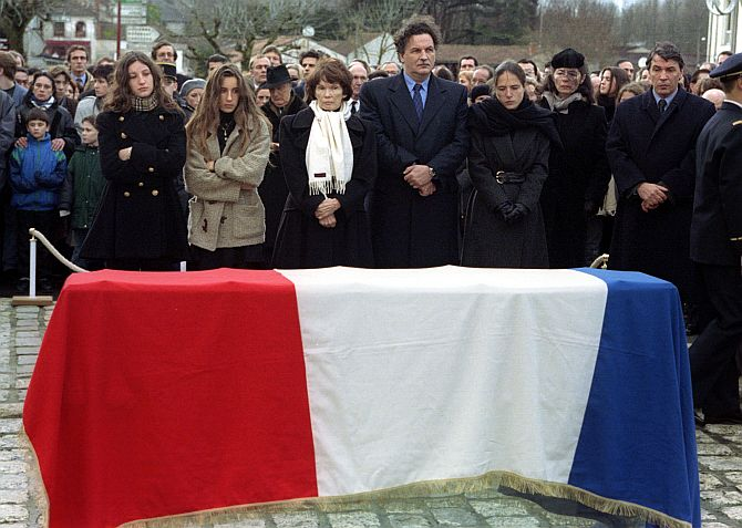 This 1996 photograph shows the Mitterrand family standing before the flag-draped coffin of former French President Francois Mitterrand during funeral ceremonies in Jarnac. L-R are: Grand-daughters Justine and Pascale, wife Danielle, son Jean-Christophe , daughter (out of wedlock) Mazarine, Mazarine's mother Anne Pingeot and other son Gilbert. At rear (with hat) behind Danielle Mitterrand is brother Robert Mitterrand
