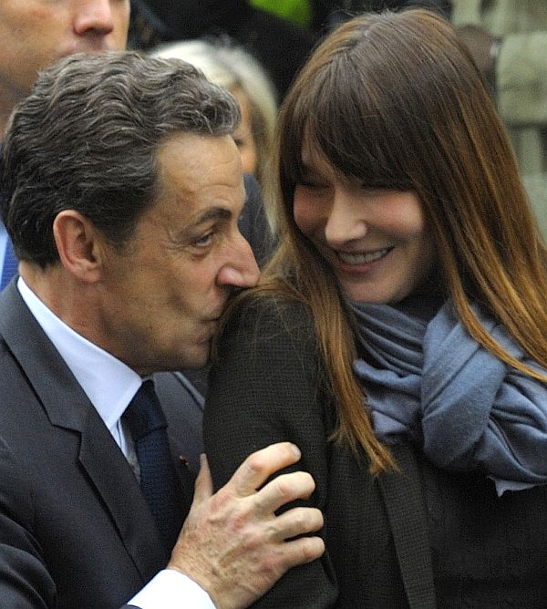 France's former president Nicolas Sarkozy kisses the shoulder of his wife Carla Bruni-Sarkozy