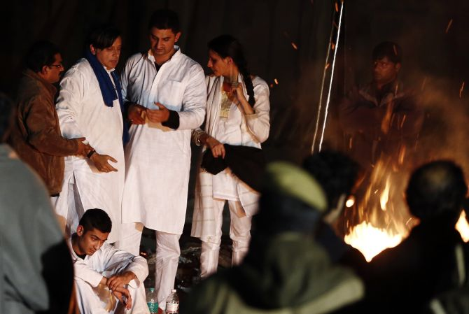 Tharoor stands next to the burning pyre of his wife Sunanda Puskhar Tharoor at a cremation ground in New Delhi, on Saturday