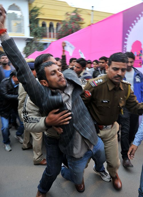 A protestor being whisked away by the police
