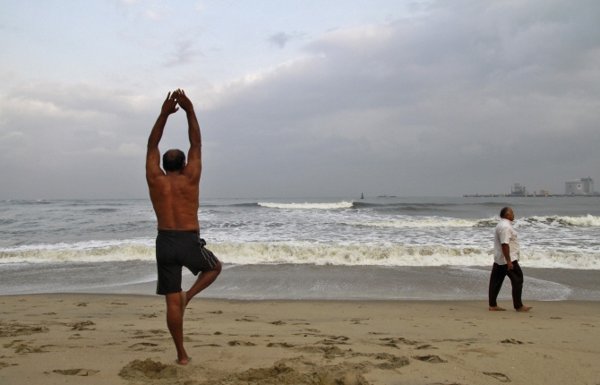 A man exercises on a beach against the backdrop of pre-monsoon clouds in Kochi