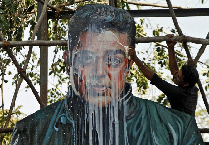 A fan of actor and director Kamal Haasan pours milk on his cardboard cutout to celebrate the release of his new movie in Chennai.