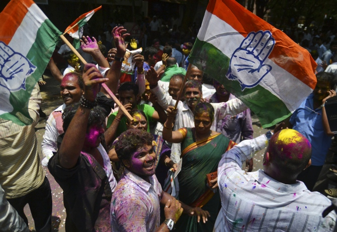 Supporters of India's ruling Congress party celebrate as they hold their party flags outside a vote counting centre in Bangalore