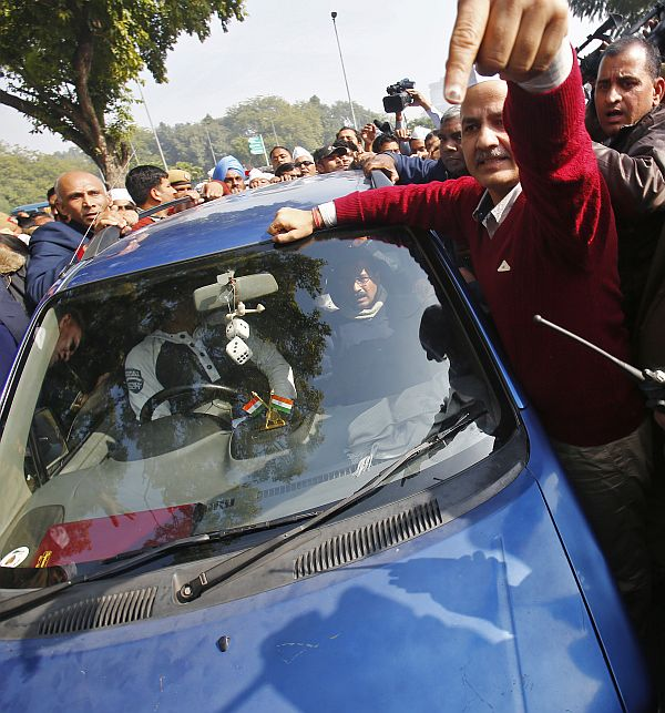 AAP leader Manish Sisodia (in red) gestures near the car carrying Delhi Chief Minister Arvind Kejriwal