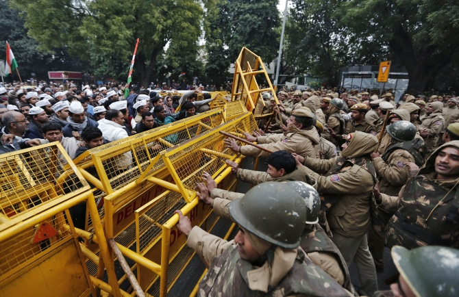 Supporters of the Aam Aadmi Party push barricades installed by the police during a protest in New Delhi
