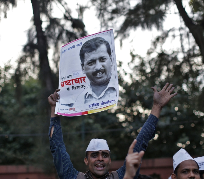 A supporter of the Aam Aadmi Party holds a portrait of Delhi's chief minister Arvind Kejriwal during a protest in New Delhi