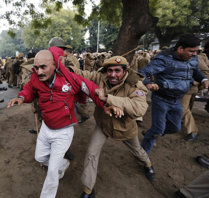 A policeman drags a supporter of the Aam Aadmi Party from the site of a protest led by Delhi Chief Minister Arvind Kejriwal in New Delhi