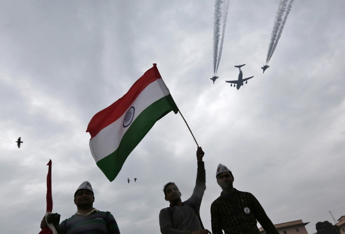 A supporter of the Aam Aadmi holds up India's national flag during a protest, as Indian Air Force aircrafts fly past as part of Republic Day rehearsals, in New Delhi