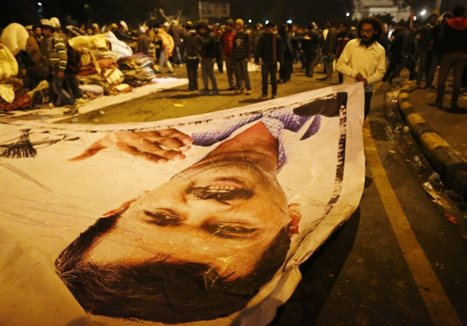 A supporter of Aam Aadmi Party removes a poster with a portrait of Delhi Chief Minister Arvind Kejriwal from the site of a protest after Kejriwal called off the sit-in protest against the police in New Delhi