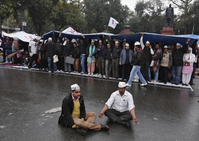 Supporters of the Aam Aadmi Party take part in a sit-in protest as others use a sheet to protect themselves from the rain in New Delhi