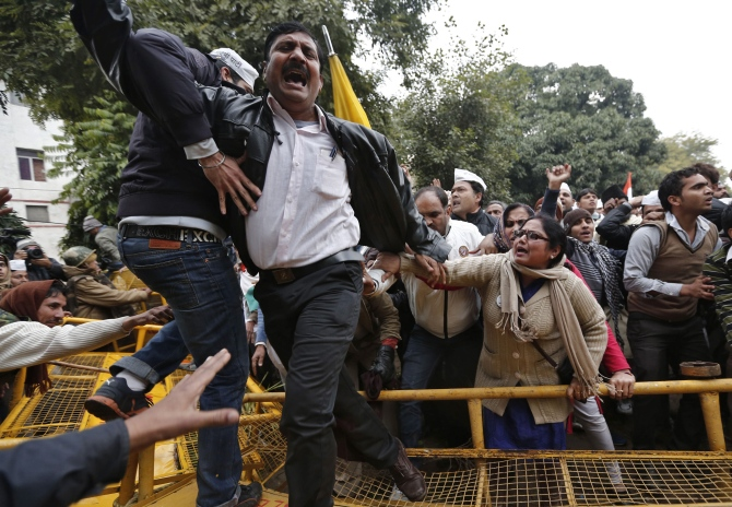 A supporter of the Aam Aadmi Party shouts slogans as he climbs over a police barricade during a protest led by Delhi Chief Minister Arvind Kejriwal in New Delhi