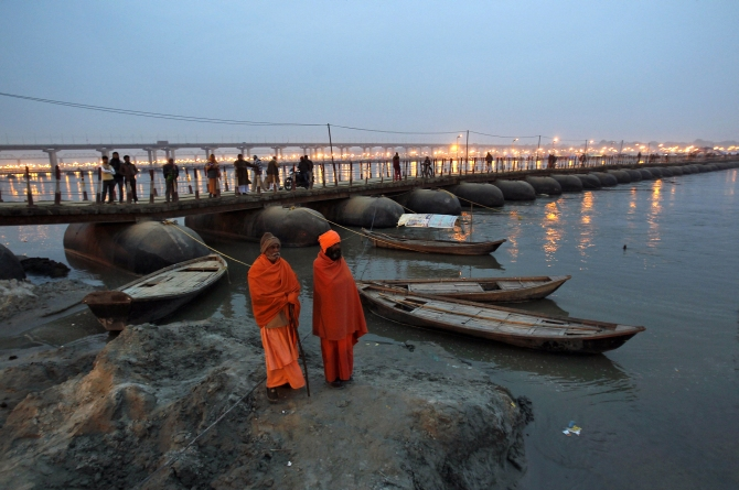 Sadhus or Hindu holy men stand on the banks of river Ganges next to a pontoon bridge in Allahabad