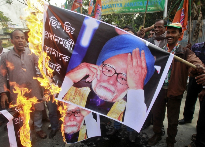 Activists from the Bharatiya Janata Party shout slogans as they burn banners with images of India's Prime Minister Manmohan Singh during a protest in Agartala