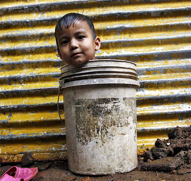 A boy waits for his mother to fetch water from a nearby hand pump to bathe him, outside a makeshift hut in Chennai.