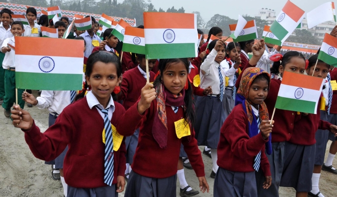 School children wave flags during the Republic Day celebrations in Guwahati, Assam