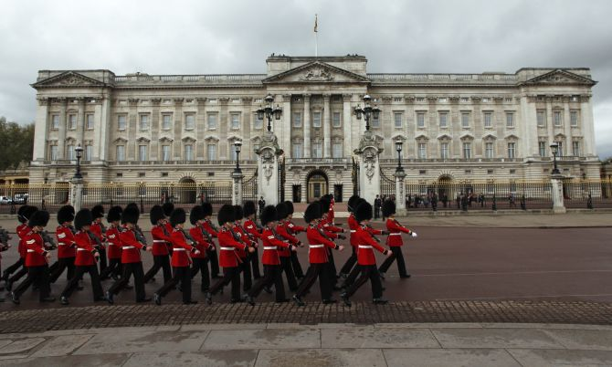 Royal guards march past the Buckingham Palace in London