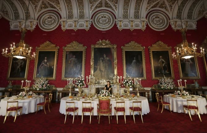 A curator poses while rearranging the coronation banquet exhibit during a media preview of the exhibition The Queen's Coronation 1953 at Buckingham Palace