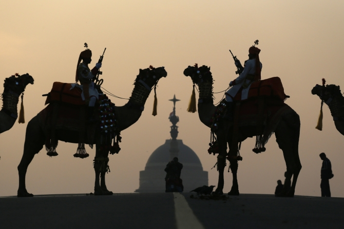 Border Security Force soldiers ride their camels in front of India's presidential palace Rashtrapati Bhavan during a rehearsal for the 'Beating the Retreat' ceremony in New Delhi