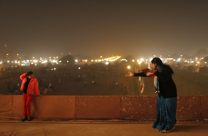A mother directs her daughter to pose for a photo at the venue for the 'Beating the Retreat' ceremony in New Delhi.