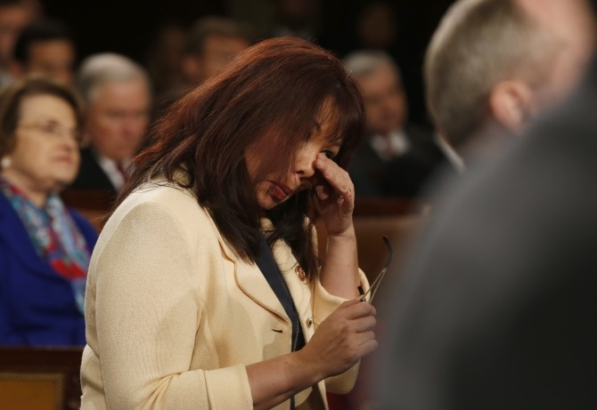 US Representative Tammy Duckworth wipes tears from her eyes during a standing ovation for US Army Ranger Sgt First Class Cory Remsburg, injured while serving in Afghanistan, who was a guest in first lady Michelle Obama's box during President Barack Obama's State of the Union speech on Capitol Hill