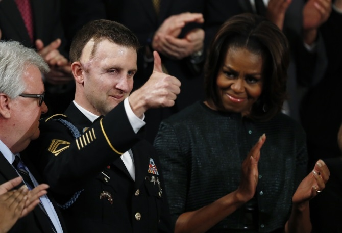 US first lady Michelle Obama applauds US Army Ranger Sgt. First Class Cory Remsburg, injured while serving in Afghanistan