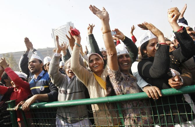 Supporters of Aam Aadmi Party cheer after its leader Arvind Kejriwal took an oath as the new chief minister of Delhi.