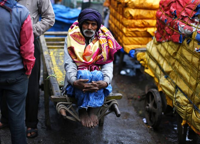 A labourer sits on a cart during a cold morning in Delhi