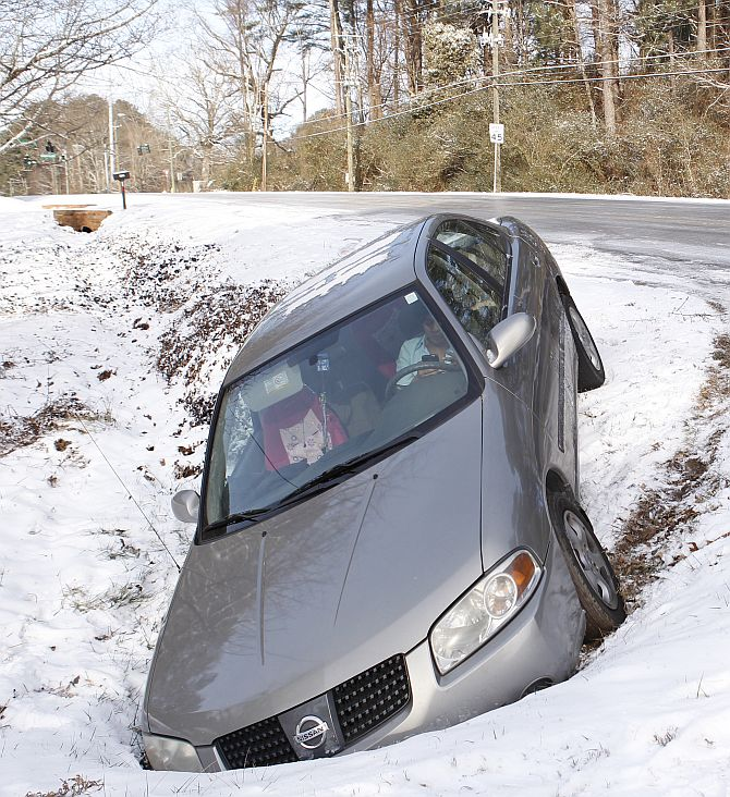 A driver uses a mobile phone in a car after running off the roadway due to a snow storm in Atlanta, Georgia