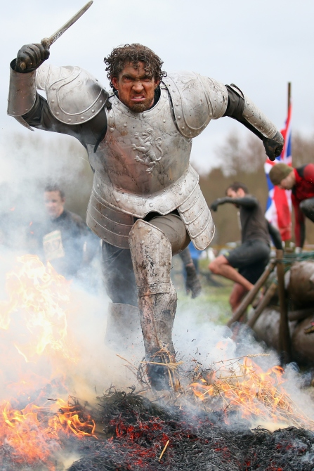 A competitor dressed as a knight runs through a fire during the Tough Guy Challenge in Telford, England