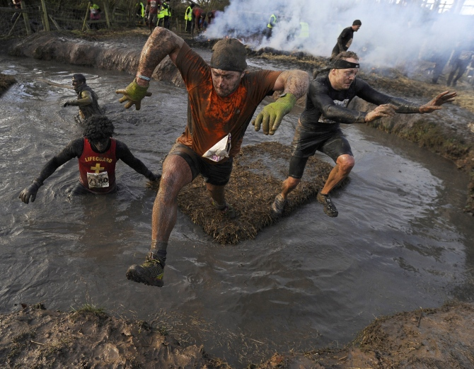 Competitors jump across water during the Tough Guy event.