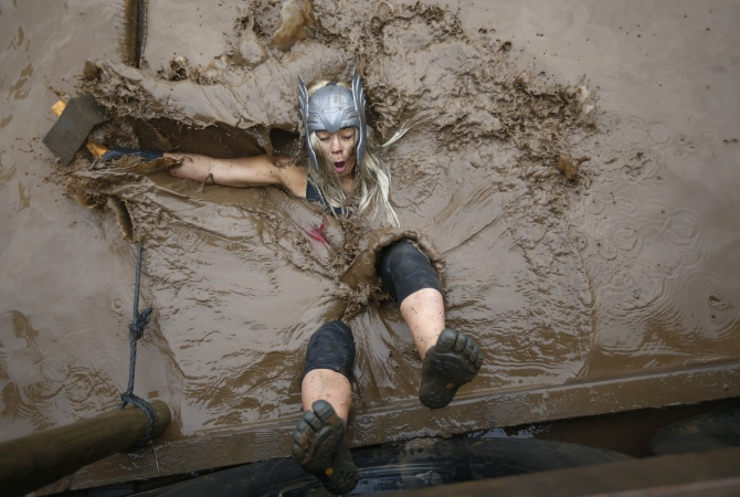 A competitor falls in to muddy water during the Tough Guy event.