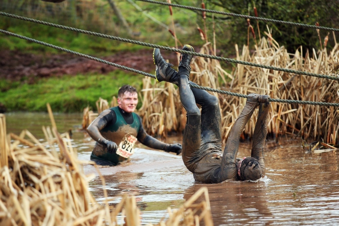 A competitor tries to avoid the water during the Tough Guy Challenge in Telford, England