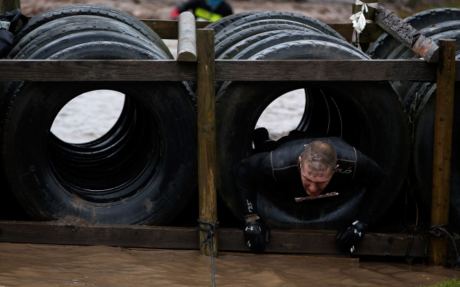A participant pulls himself through some tyres during the Tough Guy Challenge in Telford, England